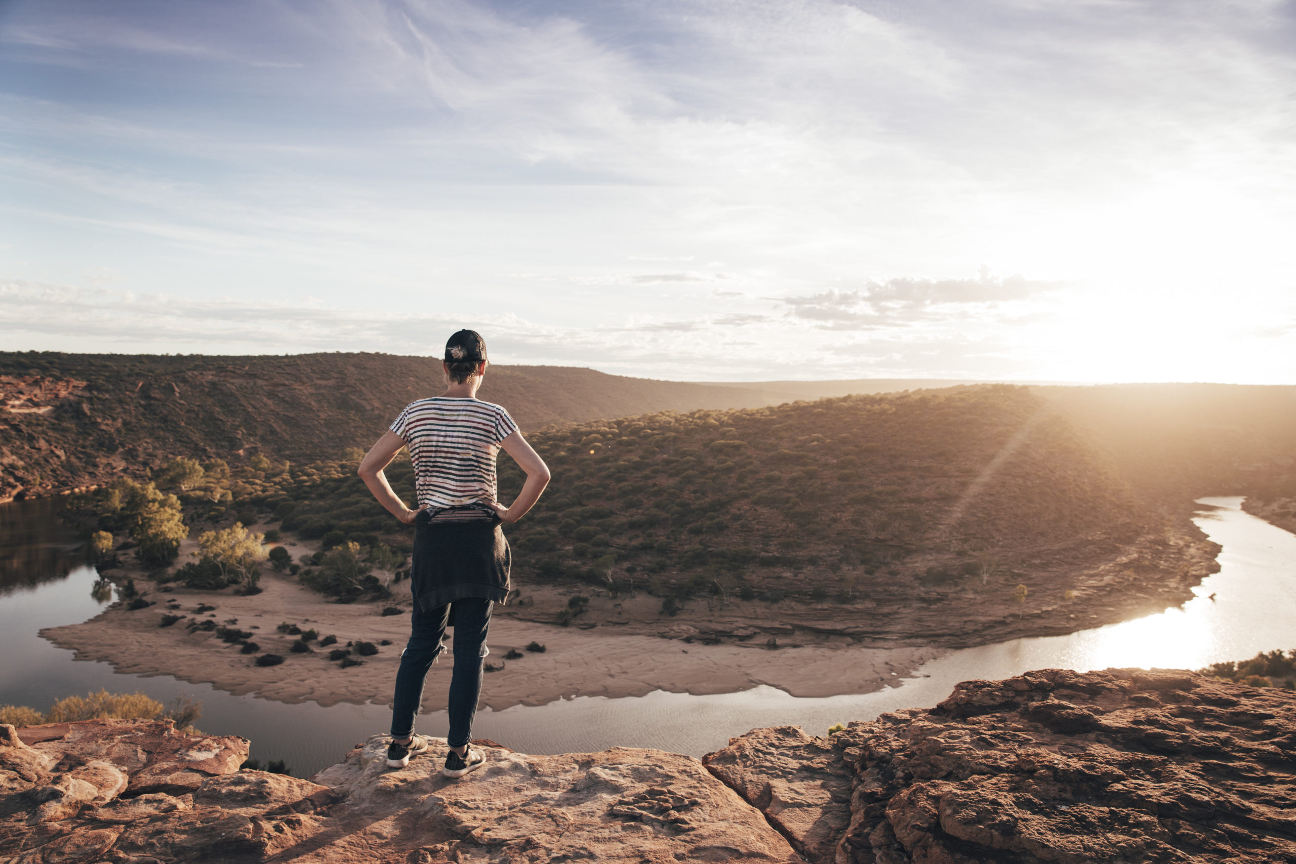 A woman looks out at a river in a desert
